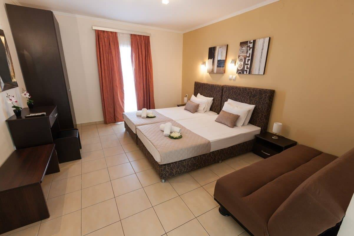 The double bed, sofa, mirror, wardrobe and exit to balcony in the Aphrodite studio