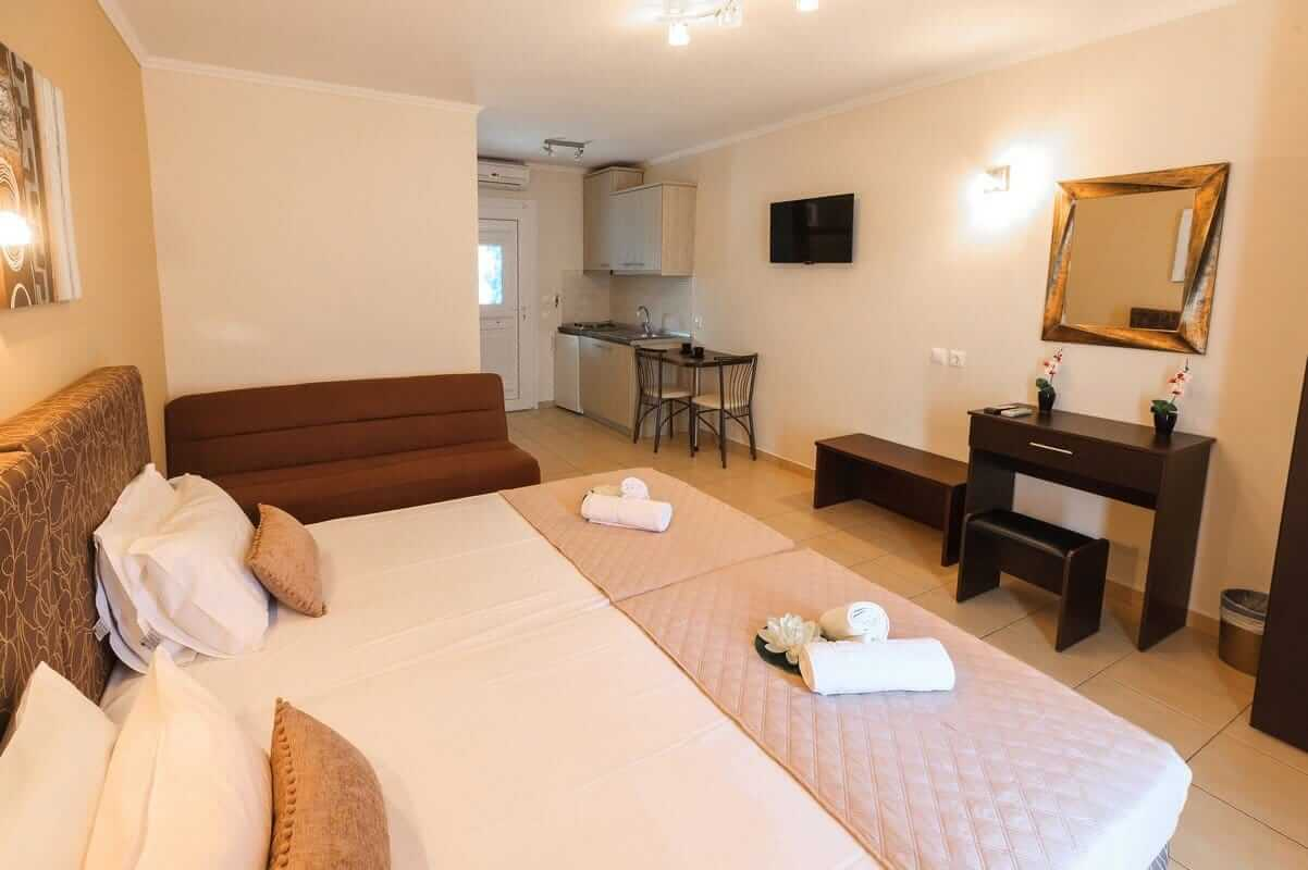 The double bed, sofa, mirror and kitchen in the Aphrodite studio