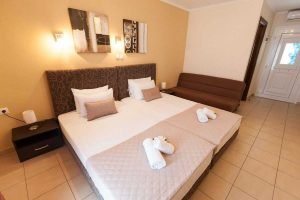 The double bed, sofa, entrance to bathroom and main door of Aphrodite studio