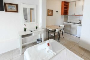 The table, kitchen, the single bed and entrance to the bathroom in the Artemis studio