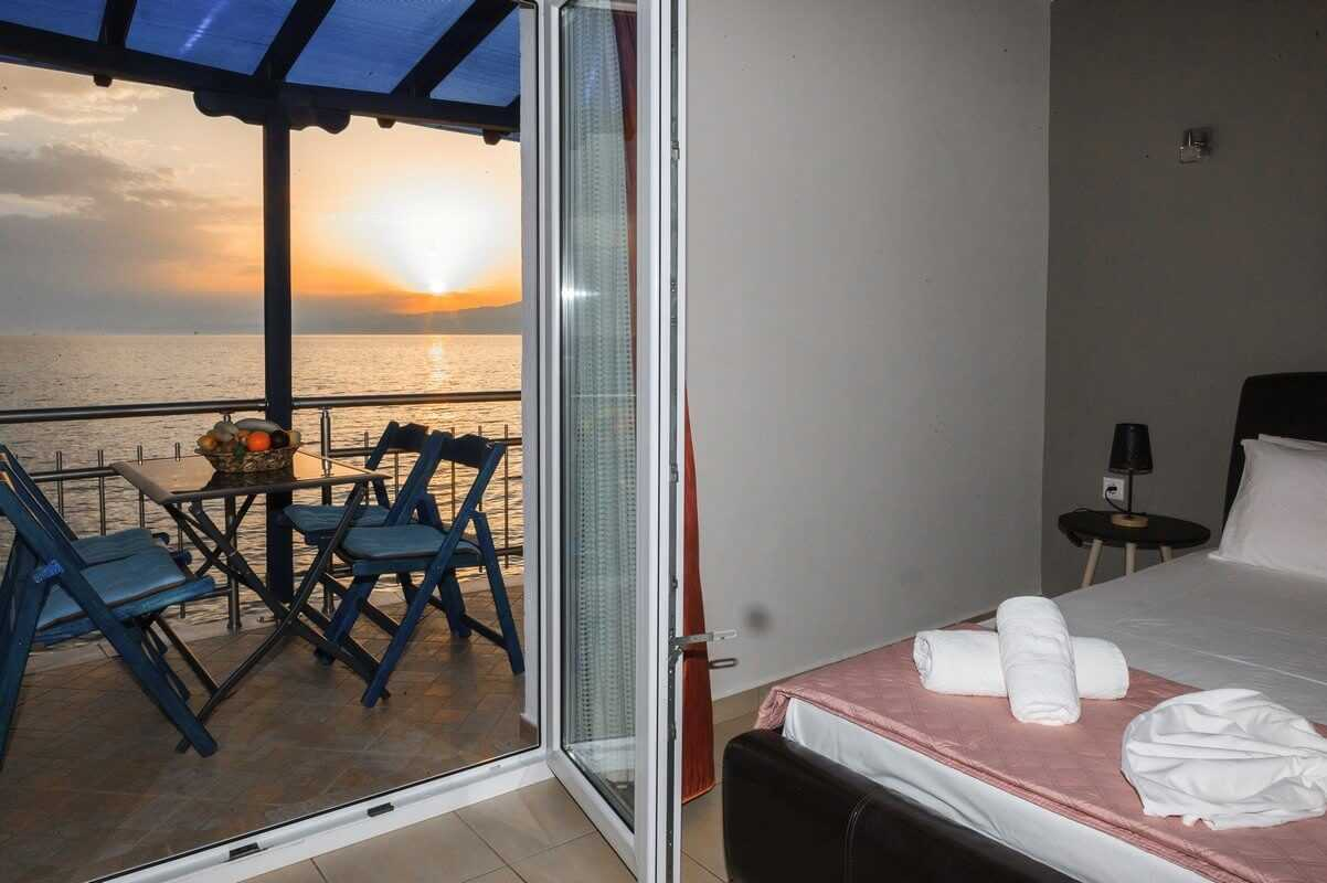 The double bed, the table in the balcony of Zeus and the view in the Aegean during sunset