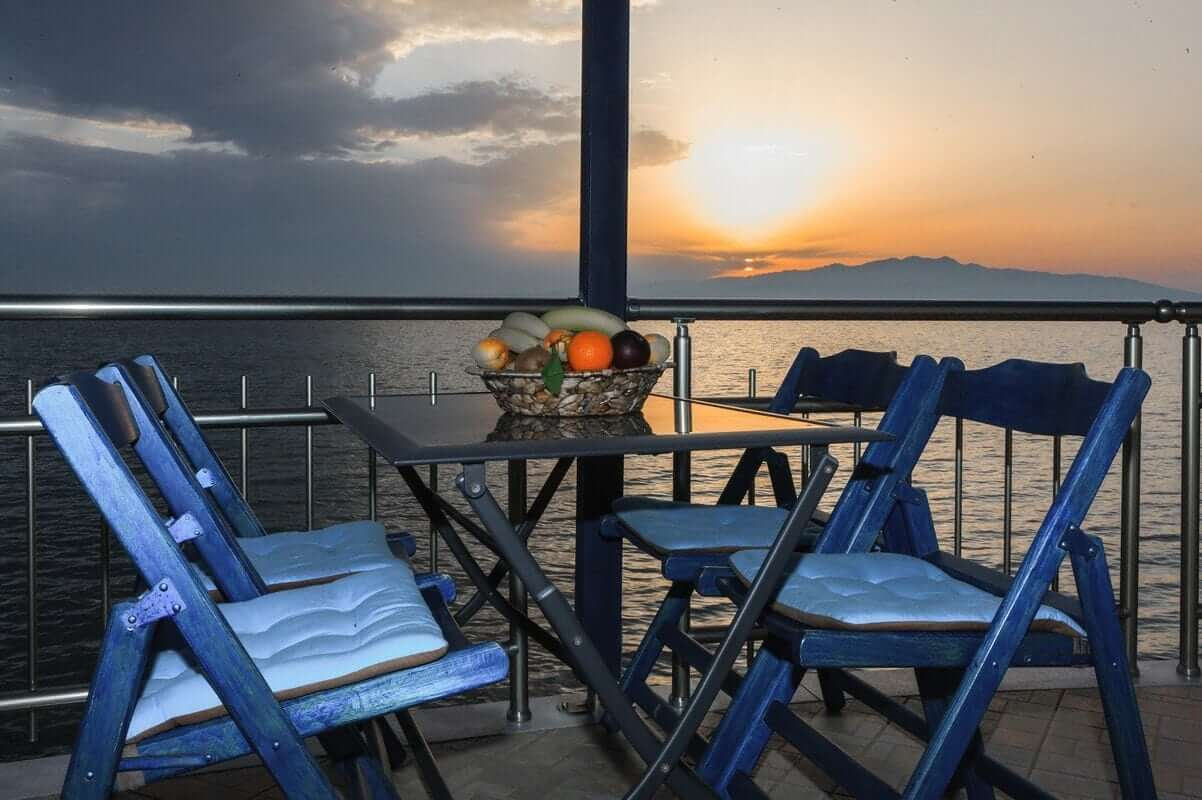 The table in the balcony of Zeus and the view in the Aegean during sunset