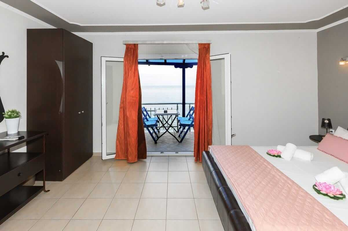 The double bed and the view from the balcony in the Zeus Apartment
