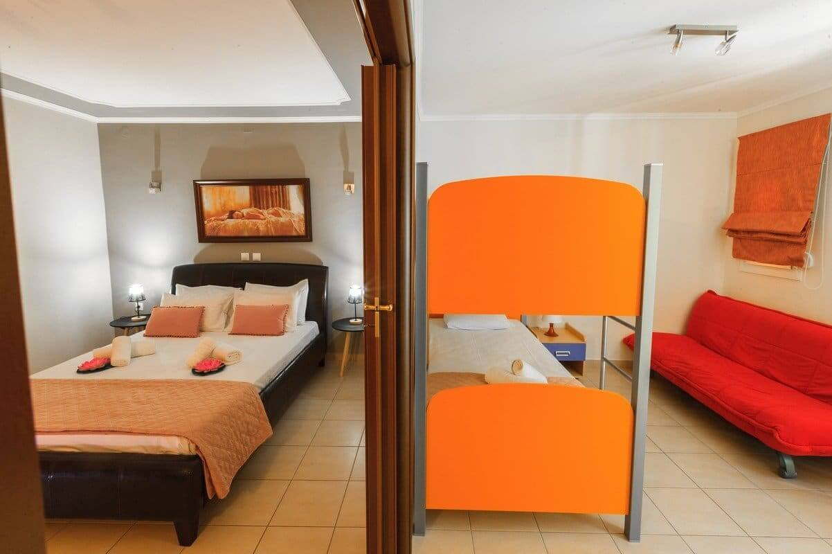 The two rooms of the Zeus apartment: the double bed from one side and the bunk and sofa bed from the other side