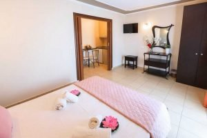 The double bed, wardrobe and kitchen in the Zeus apartment