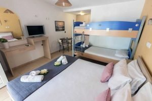 The double bed, bunk bed, table and tv of the Filoxenia Family studio