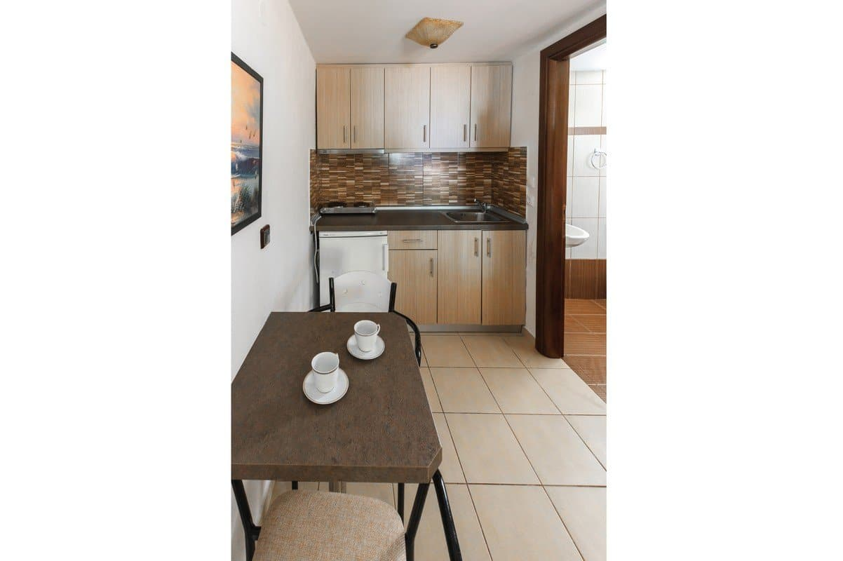 The kitchen, toilet entrance and table in the Filoxenia Family studio